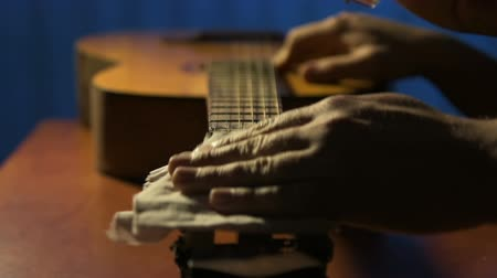 Former guitarist gently rubs head of fretboard of old acoustic guitar