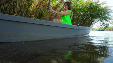 приморский : Young woman takes selfie with tablet on background of wide river Стоковые видеозаписи