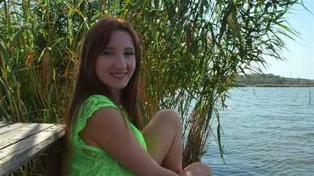 çekicilik : Young woman in green dress smiles and enjoys life on river bank in provincial town