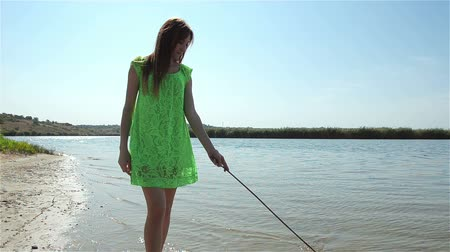 çekicilik : Young woman walks along river and leads stick on water