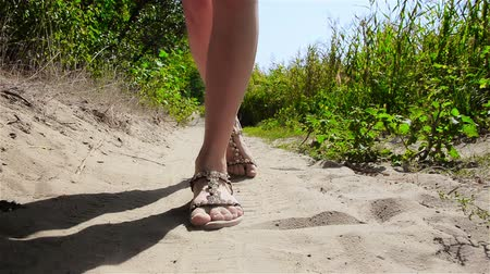 falu : Young woman is walking on sand. Close up view on legs