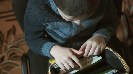 školka : Young schoolboy in his room is looking fornecessary notebook in his bag