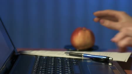 sending : Closeup of woman at office clicks on keys of laptop and biting big apple