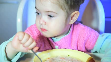 yummy face : Little girl is eating soup from plate