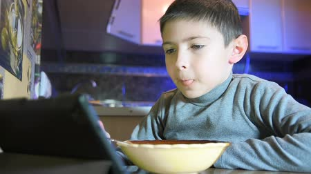jíst : Schoolboy eats snacks with milk and watches video clips on tablet pc
