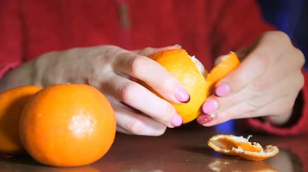 hladový : Close up of hands of woman peeling an orange from peel