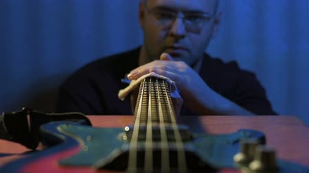 gitáros : Guitarist produces care of him musical instrument