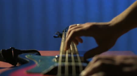 řemeslníci : Craftsman in workshop playing on strings of bass guitar and checks sound