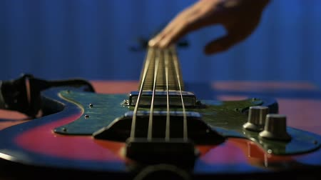 gitáros : Guitarist runs his fingers over strings of his old bass guitar