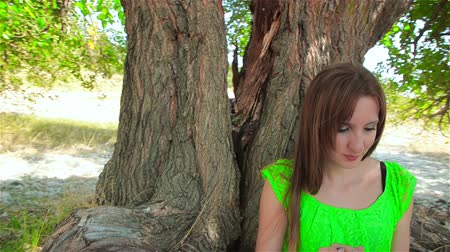 luz do dia : Young woman sits under tree and looks at tablet screen