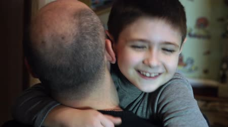 otcovství : Happy son runs to his father and hugs him by neck in slow motion
