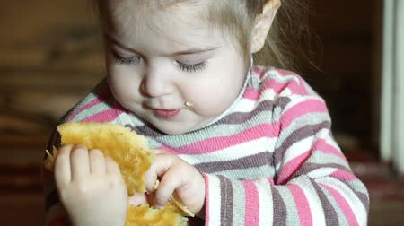 hladový : Little girl eating homemade pie in slow motion