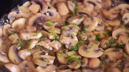 baixo teor de gordura : Brown champignons in oil on frying pan are sprinkled with dill and herbs