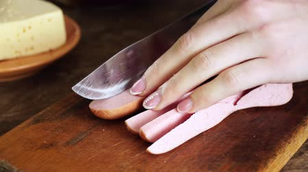 вылеченный : Woman cuts smoked sausage with sharp knife