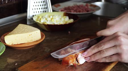 összetevők : Woman in kitchen cutting with knife chicken meat for cooking pizza