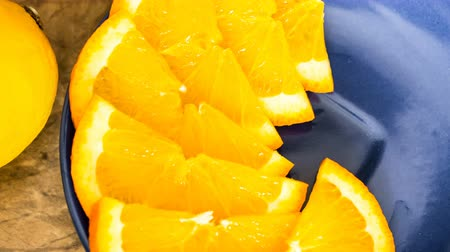 cítrico : Stop motion of appearance of orange slices on blue plate