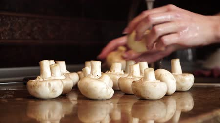 chop up : Woman washes mushroom and puts them on wooden surface