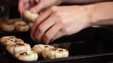 chop up : Woman puts champignons on baking sheet