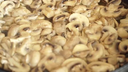 baixo teor de gordura : Fresh white champignons boil in their own juice in kitchen in frying pan