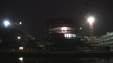 erkély : Late at night, there is building on the river bank in Amsterdam under construction