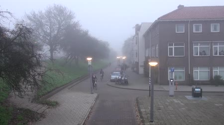 cyclists : Amsterdam city street in autumn morning the fog