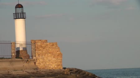 rehberlik : Old lighthouse at the shore of the sea Stok Video