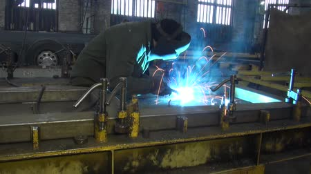 metal worker : man leaning welder. sparks from metal Stock Footage