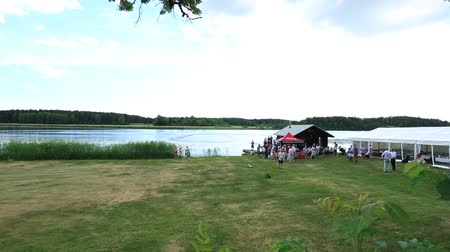jubileu : Outdoor firm party near a lake in the great summer day. Some people are playing with radio controlled cars, some are talking. Sweden, Enkoping. 9 June 2018.