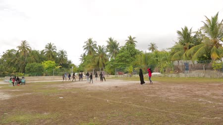 obec : Group of muslim girls are playing med ball on a field.