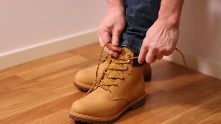 ботинок : Man in jeans putting on yellow tying shoes. People backgrounds. Стоковые видеозаписи