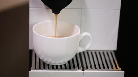 favori : Close up view of coffee running from capsule coffee machine into white cup. Beautiful backgrounds. Stok Video