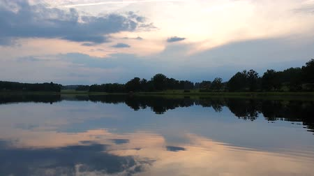 odrážející : Gorgeous summer evening. Crystal clear mirror water surface. Sky covered with heavy clouds.
