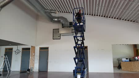 establishment : A working man on a scissor lift fixing ceiling. Construction work concept. Stock Footage