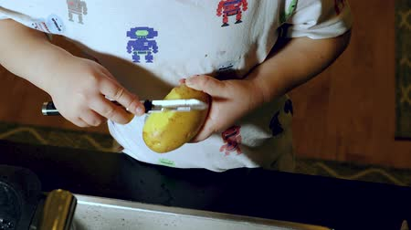 soyulması : Short film showing a child learning to peel potatoes. Children concept.