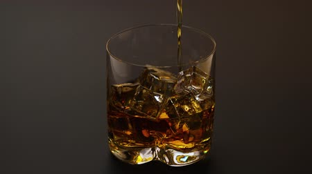 bourbon whisky : Short film showing whiskey being poured into a tumbler glass with ice on black background. Beautiful backgrounds. Alcohol concept.