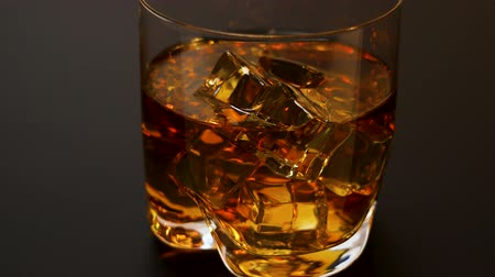 bourbon whisky : Beautiful view of slowly pulling back whiskey glass with ice cubes on black background. Alcohol and health concept,