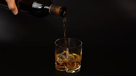 bourbon whisky : Short film showing whiskey being poured into a tumbler glass with ice on black background. Slow motion. Beautiful backgrounds. Alcohol
