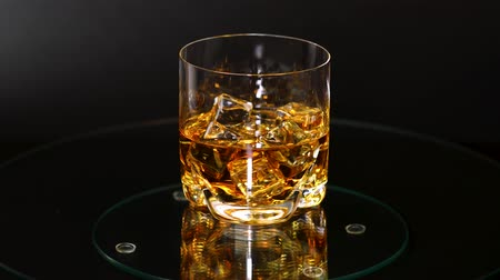 pálinka : Beautiful view of rotating glass of whiskey with ice cubes. Alcohol and health concept.