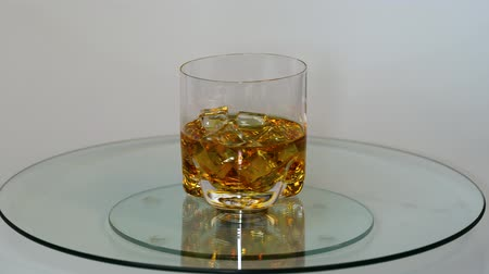 pálinka : Beautifu view of rotating glass of whiskey with ice cubes. Alcohol and health concept.