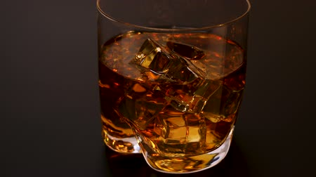 pohárek : Beautiful view of approaching glass of whiskey with ice cubes on black background. Alcohol concept. Food and drinks.