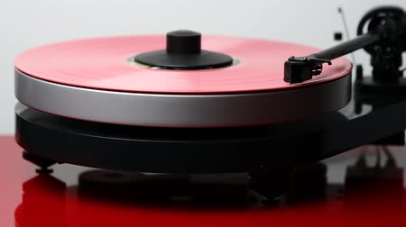 gramophone : Close up view of a man lifting up needle on pink vinyl disc on audio record player. Stock Footage