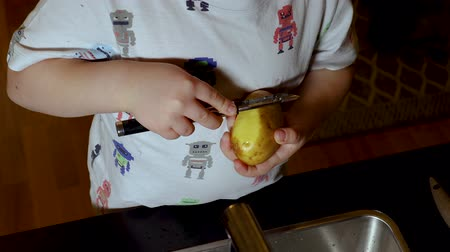 descamação : Short film showing a child learning to peel potatoes. Children concept.