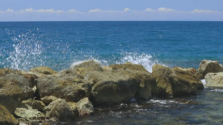 curacao : Slow motion. Gorgeous view of waves braking on stones. Turquoise water of Atlantic ocean and big rocks on blue sky background. Willemstad. Curacao. Stock Footage