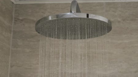Close up view of water running in shower. Modern big round contemporary rain chrome shower head. Wideo