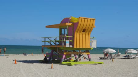 People on Miami beach on beautiful sunny day. Sand beach, tourists and yellow lifeguard tower on blue Atlantic ocean merging with blue sky background. Miami USA 24092019. Wideo