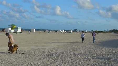 Тропический климат : People on Miami Beach relax on sandy beach a beautiful sunny day on the dark blue Atlantic Ocean merging with a blue sky background. Miami USA. 24092019.