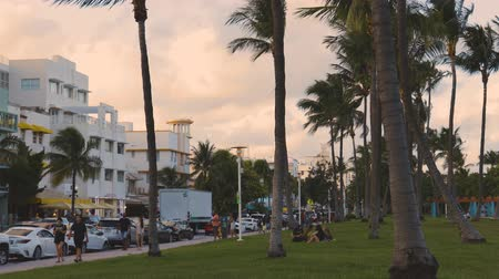 Beautiful Miami city landscape view. Beautiful hotel buildings along road full of cars, tourists walking and resting on grass under palm trees on blue sky with big white clouds background. USA Miami 240919.