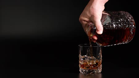 bourbon whisky : Short film showing whiskey being poured into a tumbler glass with ice on black background. Slow motion. Beautiful backgrounds. Alcohol concept.
