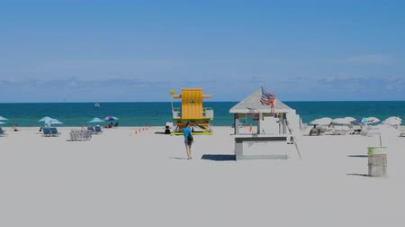 merging : People on Miami beach on beautiful sunny day. Sand beach, tourists and yellow lifeguard tower on blue Atlantic ocean merging with blue sky background. Miami USA 24092019. Stock Footage