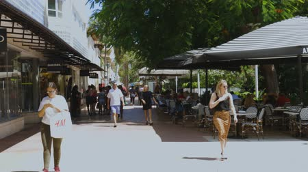 kafeterya : View of walking street of Miami city. Boutique shops, outdoor cafes, walking and resting people on big green tree background. USA Miami 24092019.